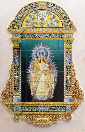 ceramica: SEVILLE, SPAIN - OCTOBER 29, 2014: The ceramic tiled Madonna by A. Morilla from 20. cent. in manufacture Ceramica Santa Ana de Triana on the fadade of church Iglesia de Santa Maria de las Nieves.