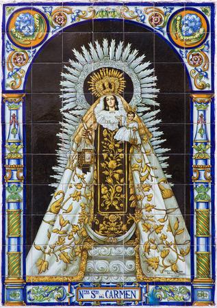 ceramica: SEVILLE, SPAIN - OCTOBER 29, 2014:  The ceramic tiled Madonna (Nostra Senora del Carmen) on facade of church Santa Catalina by Antonio Martinez Adorna from manufactory Ceramica Santa Ana de Triana. Editorial