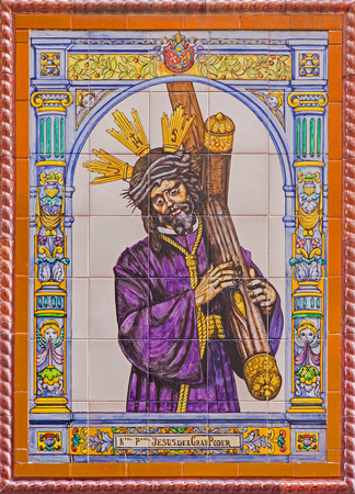 manufactory: SEVILLE, SPAIN - OCTOBER 29, 2014: The ceramic tiled Christ with the cross by manufactory Campos from Seville on the church facade.