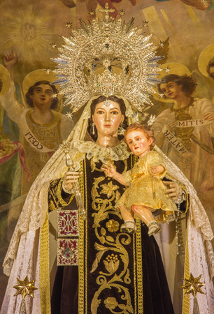 vested: SEVILLE, SPAIN - OCTOBER 30, 2014: The statue of traditional vested Madonna (Virgen of Carmen) by Rafael Barbero (1945) on the main altar of baroque church Iglesia de Buen Suceso. Editorial