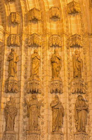 neo gothic: SEVILLE, SPAIN - OCTOBER 28, 2014: The statues of holys on the main west portal (Puerta de la Asuncion) of Cathedral de Santa Maria de la Sede from neo gothic restoration in years 1883 - 1898. Editorial