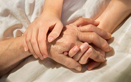 babyhood: hands of grandmother and grandchild in the bed