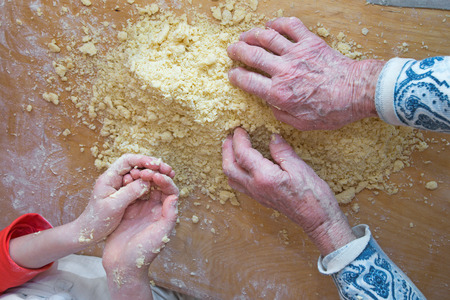 hands of grandmother and grandchild at cooking Stock Photo