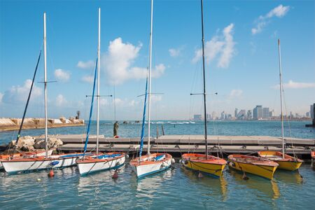 jafo: TEL AVIV ISRAEL  MARCH 2 2015: The little harbor and yachts under old Jaffa and Tel Aviv in the backgound in the morning light and man at fishing.