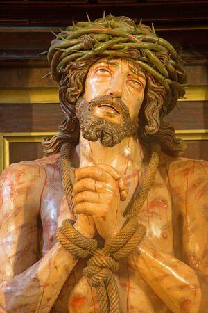 tortured: GRANADA, SPAIN - MAY 29, 2015: The tortured Jesus Christ in Bond statue in church Iglesia de los santos Justo y Pastor.