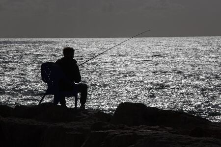 tel: The silhouette of fisher on the seaside in Tel Aviv Stock Photo
