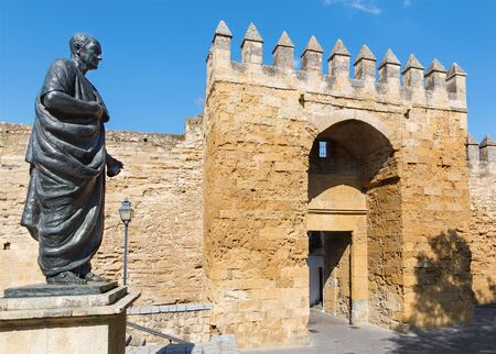 seneca: Cordoba - The statue of philosopher Lucius Annaeus Seneca the Younger by Amadeo Ruiz Olmos (1913 - 1993) and medieval gate Puerta del Almodovar.