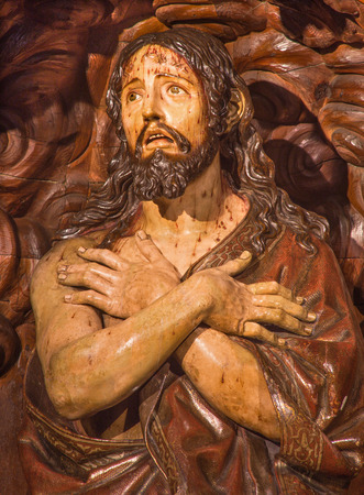 flagellation: GRANADA, SPAIN - MAY 29, 2015: The carved statue of flagellated Jesus Christ in scarleat coat in churchReal Colegiata de San Hipolito by unknown artist.