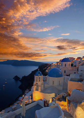 cupolas: Santorini - The look to typically blue church cupolas in Oia over the caldera and the Therasia island in the background at sunset dusk.
