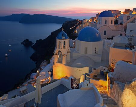 typically: Santorini - The look to typically blue church cupolas in Oia over the caldera and the Therasia island in the background at sunset dusk.