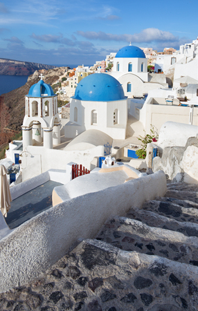 cupolas: Santorini - The look to typically blue church cupolas in Oia over the caldera and the Therasia island in the background.