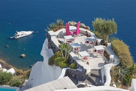 ia: Santorini - The restaurant geared to wedding romantic diner in Oia (Ia) and the yacht under cliffs in the background. Stock Photo