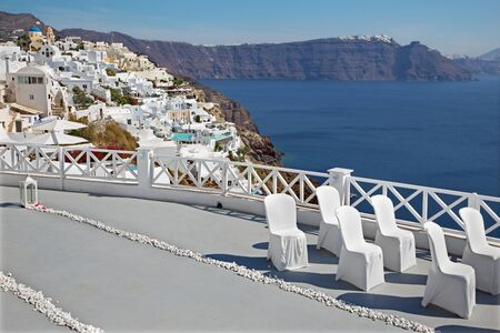 ia: Santorini - The luxury resort geared to wedding ceremony in Oia (Ia) and the caldera cliffs in the background. Stock Photo