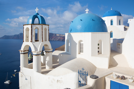 typically: Santorini - The look to typically blue church cupolas in Oia over the caldera and the Therasia island in the background.