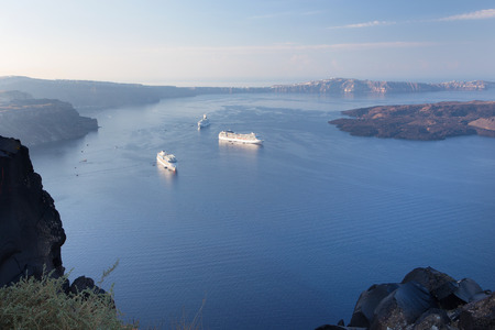 outlook: Santorini - The outlook over the Imerovigili to caldera with the cruises and Nea Kameni Island in morning light.
