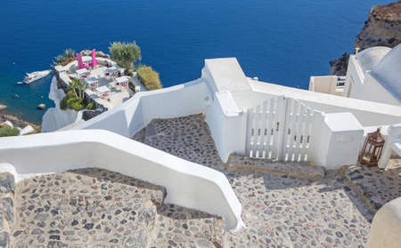 tabel: Santorini - The restaurant geared to wedding romantic diner in Oia (Ia) and the yacht under cliffs in the background. Stock Photo