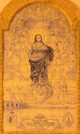 immaculate conception: CORDOBA, SPAIN - MAY 26, 2015: The ceramic tiled Immaculate Conception by Emilio and Juan Paiacios from year 2004 on the street near the Plaza de la Corredera square.