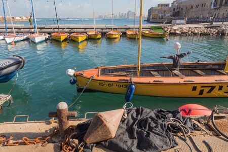 jafo: TEL AVIV, ISRAEL - MARCH 2, 2015: The little harbor and yachts under old Jaffa and Tel Aviv in the backgound in the morning light