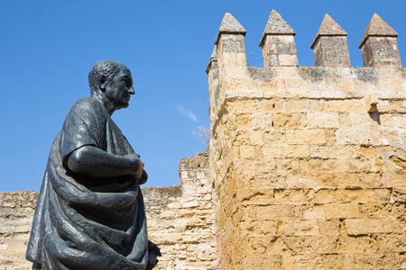 philosopher: CORDOBA, SPAIN - MAY 25, 2015: The statue of philosopher Lucius Annaeus Seneca the Younger by Amadeo Ruiz Olmos (1913 - 1993) and medieval gate Puerta del Almodovar. Editorial