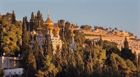 mount of olives: Jerusalem - The Russian orthodox church of Hl. Mary of Magdalene on the Mount of Olives and the cementery in sunset light. Stock Photo