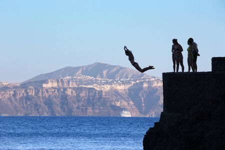 jumpers: SANTORINI, GREECE - OCTOBER 5, 2015: The young jumpers little on the coast under Oia.