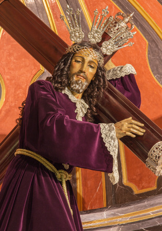 vested: MALAGA, SPAIN - MAY 31, 2015: The traditional vested statue of Jesus with the cross in church Iglesia del Santiago Apostol by unknown artist.