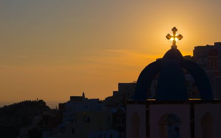 typically: Santorini - The silhouett of typically church cupolas in Oia in the sunset sun. Editorial