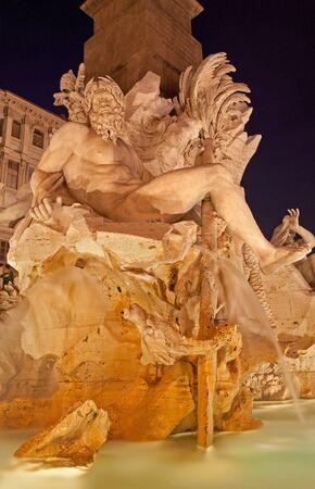 bernini: Rome - Piazza Navona and Fontana dei Fiumi by Bernini at night . Stock Photo