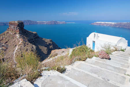 typically: Santorini - The look to typically little church Agios Ioannis Katiforis in Imerovigli and the Skaros castle. Stock Photo