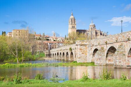 SALAMANCA, SPAIN, APRIL - 17, 2016: The Cathedral and bridge Puente Romano over the Rio Tormes river.