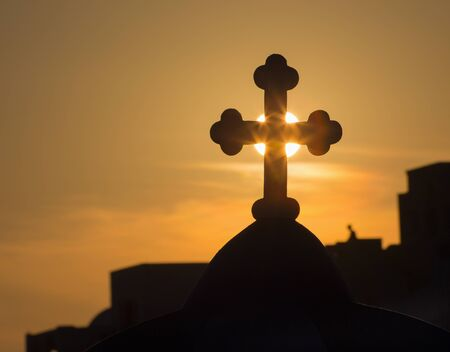 typically: Santorini - The silhouette of the cross on typically church cupolas in Oia in the sunset sun. Stock Photo