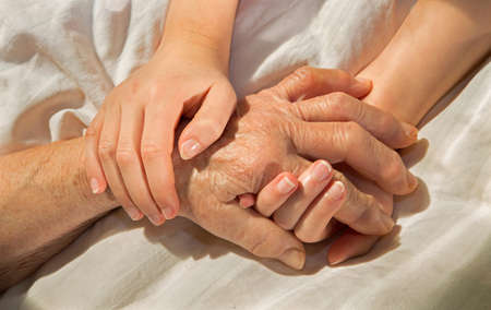 malady: hands of grandmother and grandchild in the bed