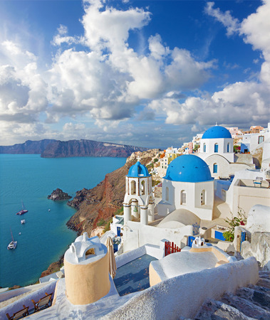 Santorini - The look to typically blue church cupolas in Oia over the caldera and the Therasia island in the background.