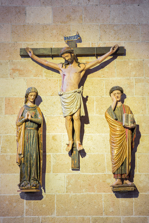 affiliation: SEGOVIA, SPAIN, APRIL - 14, 2016: The polychrome gothic sculptural group of Crucifixion in Cathedral Nuestra Senora de la Asuncion by unknown artist of 15. cent.