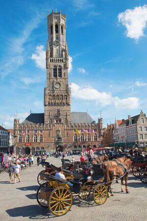 BRUGGE, BELGIUM - JUNE 13, 2014: The Carriage on the Grote Markt and Belfort van Brugge in background.