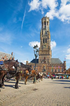 belfort: BRUGGE, BELGIUM - JUNE 13, 2014: The Carriage on the Grote Markt and Belfort van Brugge in background.