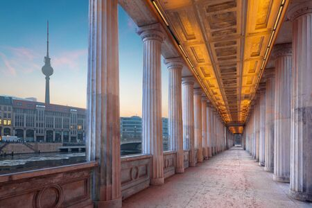 Berlin - The neoclassical porticoes of building of Old National Gallery on the riverside and Fernsehturm tower in background in morning. Editorial