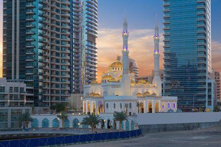 Dubai - The evening promenade of Marina and the mosque. Stock Photo