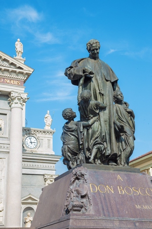 TURIN, ITALY - MARCH 15, 2017: The statue of Don Bosco the founder of Salesians in front of Basilica Maria Ausilatrice (Basilica of Mary Help) by  Gaetano Cellini (1914).