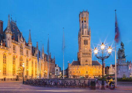 Brujas - Grote markt en el atardecer. Belfort van Brugge y los edificios Provinciaal Hof y el memorial de Jan Breydel y Pieter De Coninck. Foto de archivo - 83857223