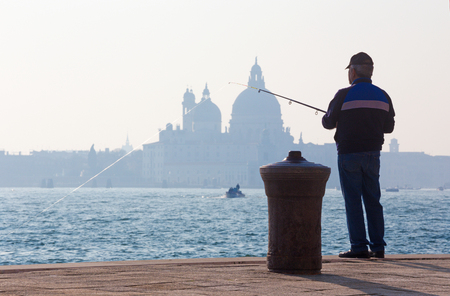 venice: VENICE, ITALY - MARCH 14, 2014: Fisherman from Riva S. Biagio waterfront and silhouette of Santa Maria della Salute church.