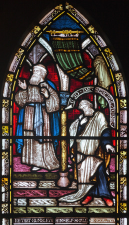 LONDON, GREAT BRITAIN - SEPTEMBER 19, 2017: The parable The Prayers of Pharisees and Tax Collectors in the temple on the stained glass in St Mary Abbots church on Kensington High Street.