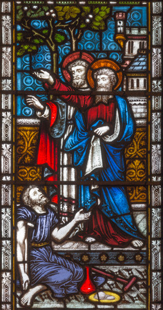 LONDON, GREAT BRITAIN - SEPTEMBER 19, 2017: The apostles Peter and John heal of paralytic in front of Temple in Jerusalem on the stained glass in St Mary Abbot's church on Kensington High Street