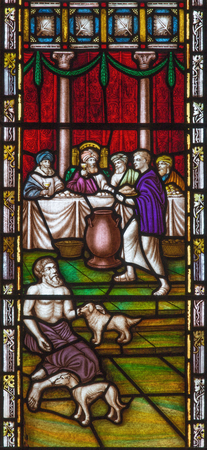 LONDON, GREAT BRITAIN - SEPTEMBER 19, 2017: The Parable of Rich man and Lazarus on the stained glass in St Mary Abbots church on Kensington High Street.