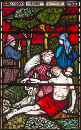 LONDON, GREAT BRITAIN - SEPTEMBER 19, 2017: The Parable of the Good Samaritan  on the stained glass in St Mary Abbots church on Kensington High Street.