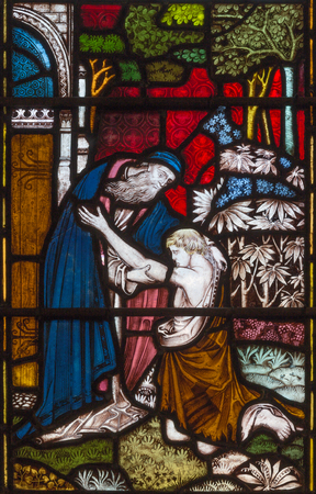 LONDON, GREAT BRITAIN - SEPTEMBER 19, 2017: The parable of the Prodigal Son  on the stained glass in St Mary Abbots church on Kensington High Street.