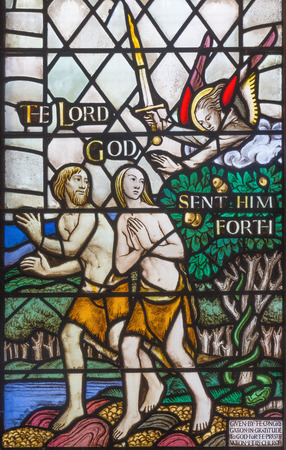 LONDON, GREAT BRITAIN - SEPTEMBER 17, 2017:  The Expulsion of Adam and Eve from Paradise on the stained glass  in church St. Barnabas by Martrin Travers 1945. Editorial