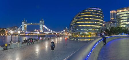 London - The panorama of the Tower bridge, promenade with the the modern Town Hall building at dusk. Stock Photo