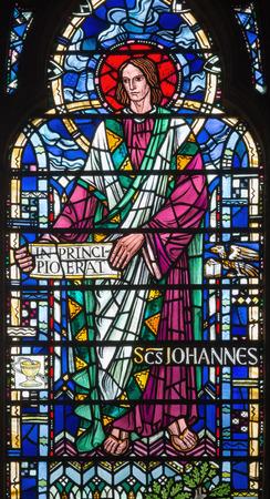 LONDON, GREAT BRITAIN - SEPTEMBER 16, 2017: The St. John the Evangelist on the stained glass in church St Etheldreda by Joseph Edward Nuttgens (1952).
