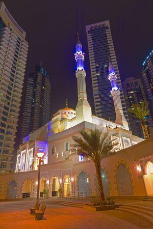 Dubai - The nightly promenade of Marina and the mosque. Stock Photo